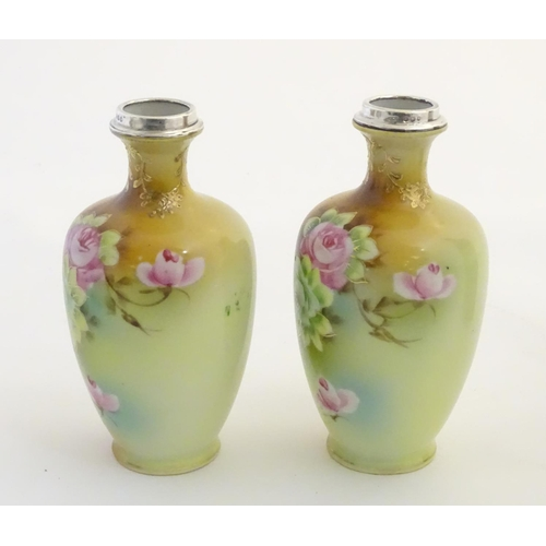 24 - A pair of small Japanese baluster vases with hand painted floral decoration, gilt highlights and sil...