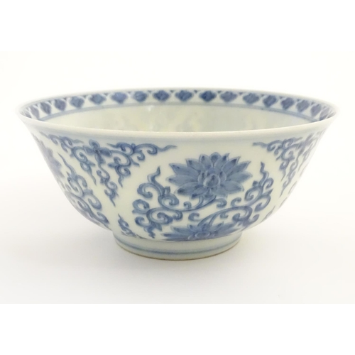 27 - A Chinese blue and white bowl decorated with flowers and scrolling vines. Character marks to base. A...
