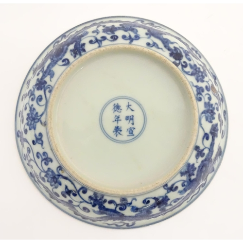 28 - A Chinese blue and white dish decorated with dragons, and scrolling flowers. Character marks to base...