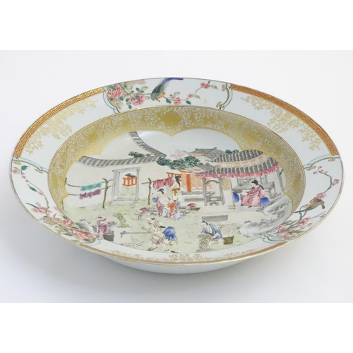 3 - A large Chinese bowl with hand painted scenes of rural life, including a mother and child, figures f...