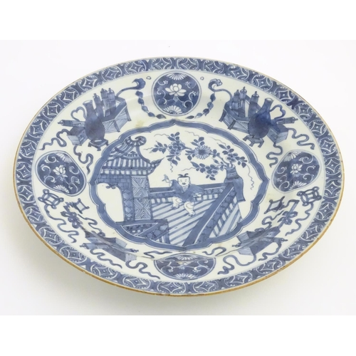 31 - A 19thC Chinese blue and white dish, decorated with auspicious artifacts such as scrolls, vases and ...