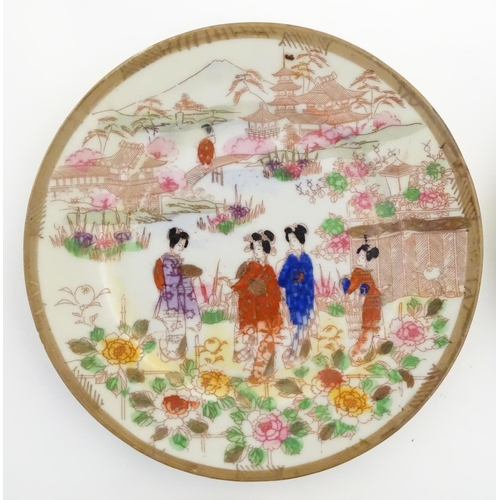 38 - Six Japanese plates depicting figures in traditional dress in an Oriental landscape depicting Mount ...