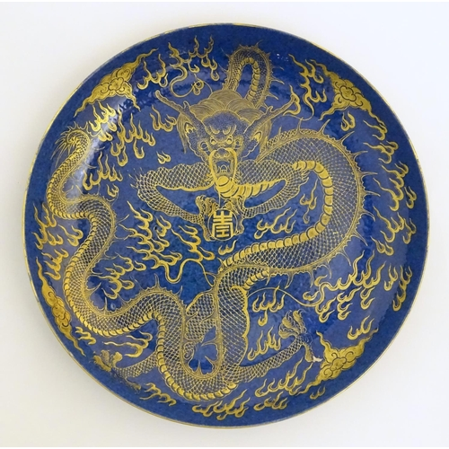 4 - A Chinese dish decorated with a gilt dragon on a blue ground. Approx. 10 1/4'' diameter....