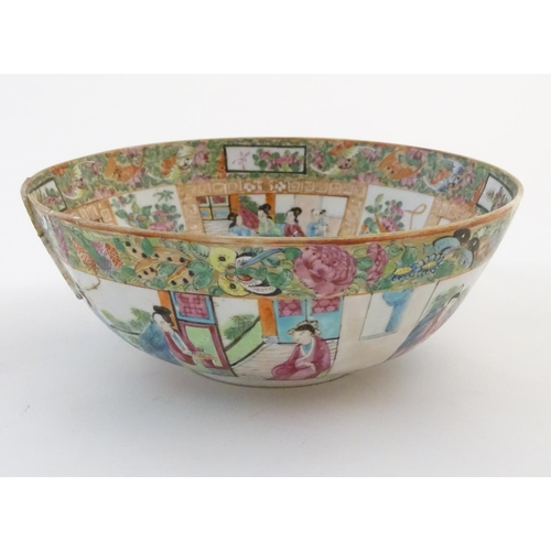 41 - A Cantonese famille rose bowl with panelled decoration depicting figures in traditional dress in var...