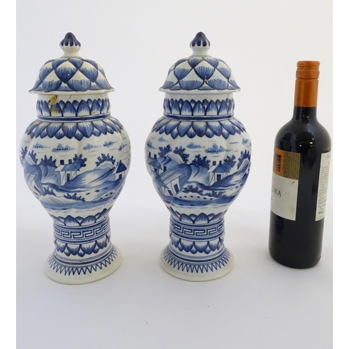 46 - Two blue and white ginger jars decorated with buildings in a landscape, and banded petal and geometr...