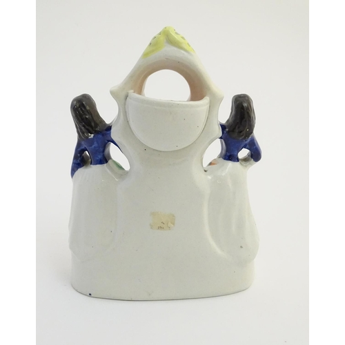 50 - A Victorian Staffordshire pottery pocket watch holder formed as a flatback figural group depicting t...