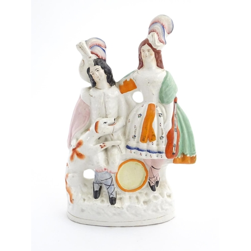52 - A Staffordshire pottery figural group of two figures with instruments in formal wear and plumed hats...