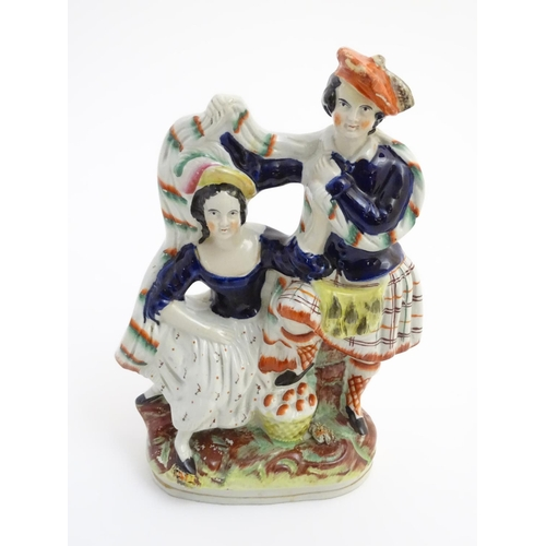 53 - A Victorian Staffordshire pottery figural group of a man and a woman in highland dress, he is wearin...