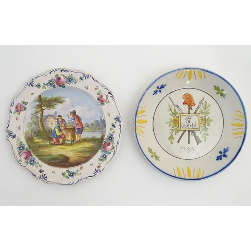 56 - Two French faience plates. One commemorating the French Revolution, decorated with a crossed bayonet...