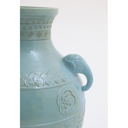 6 - A Chinese celadon baluster vase with twin handles formed as elephant heads, decorated with scrolling...