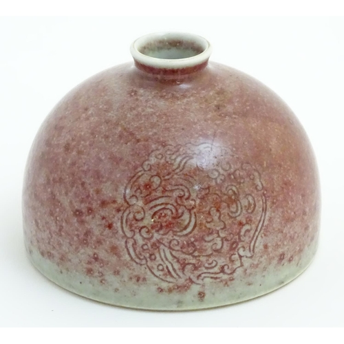 9 - A Chinese sang-de-boeuf pot/taibai zun formed as a dome, decorated with three stylised dragon rounde...