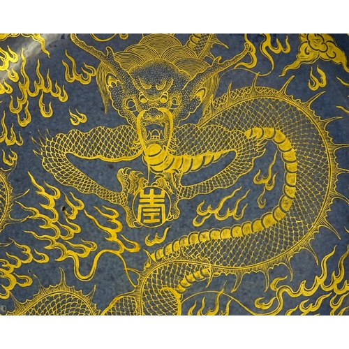 20 - A Chinese dish decorated with a gilt dragon on a blue ground. Approx. 10 1/4'' diameter....