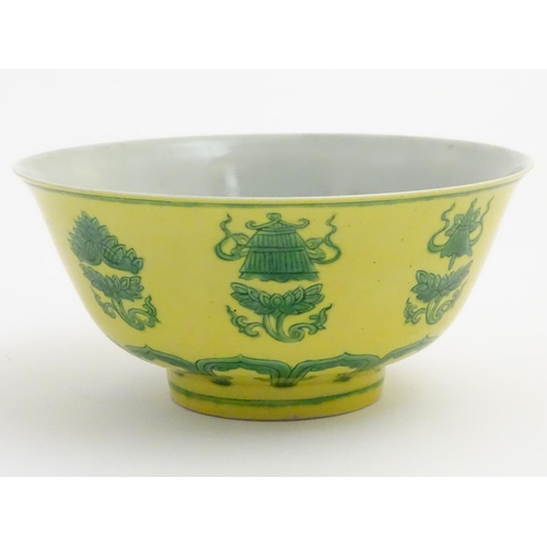 24 - A Chinese bowl decorated with green auspicious motifs above scrolling lotus flowers on a yellow grou...