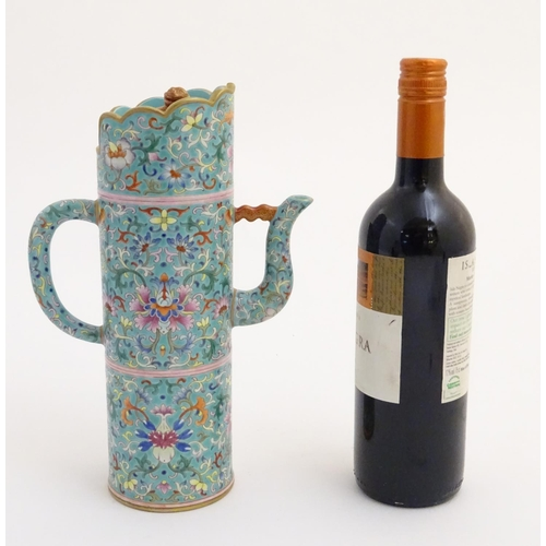 27 - A Chinese famille rose, Tibetan style tubular lidded wine ewer with a scrolling lotus design on a tu...