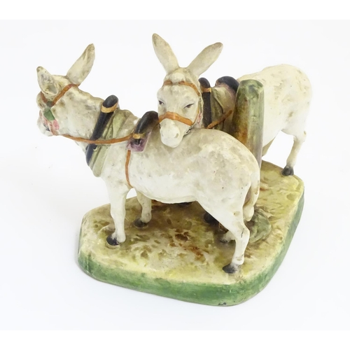 41 - A Royal Dux style figure group of two standing donkeys on a base. Incised under '1116'. Approx. 6 ½'...