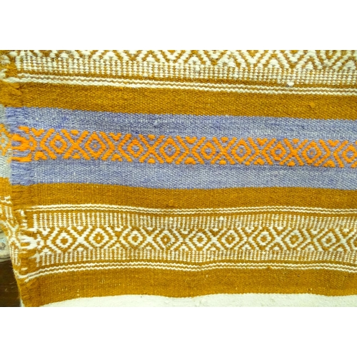 21 - A rug with orange, blue and white ground...