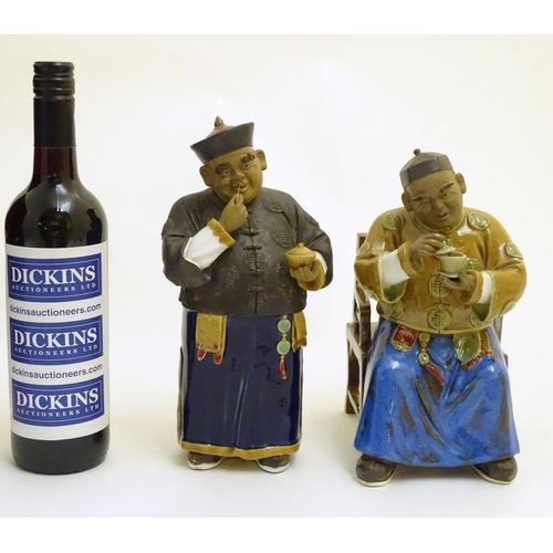 57 - Two ceramic figures of Chinese men in traditional dress drinking tea, one seated, the other standing...
