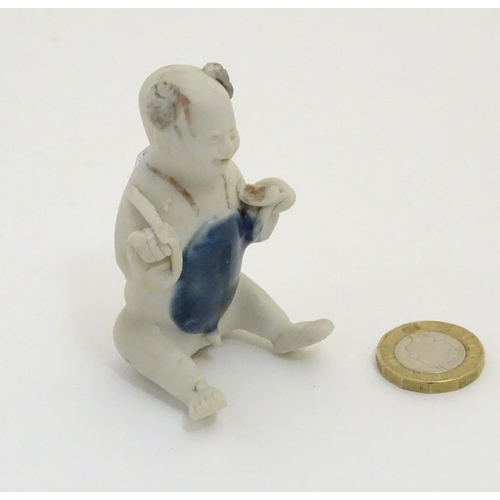 58 - An 18thC Chinese porcelain figure of a naked boy seated with his legs stretched forward and his arms...