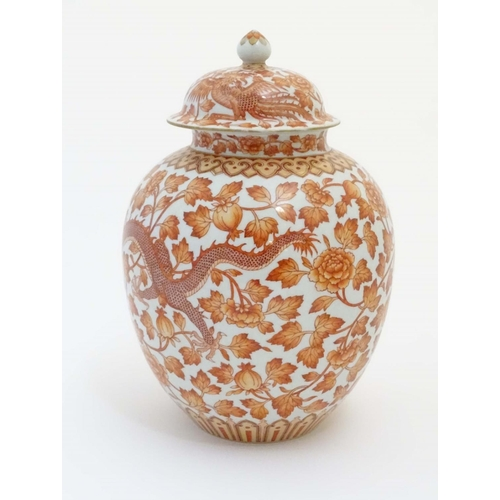 32 - A Chinese orange and white lidded ginger jar decorated with dragons, phoenix birds and scrolling flo...