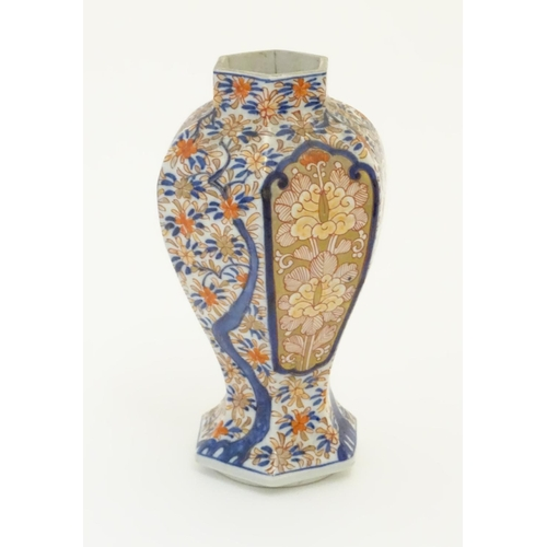 36 - An Imari style hexagonal vase with panelled floral decoration and gilt highlights. 7 1/2'' high....