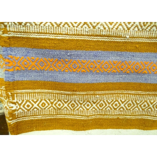 17 - A rug with orange, blue and white ground...