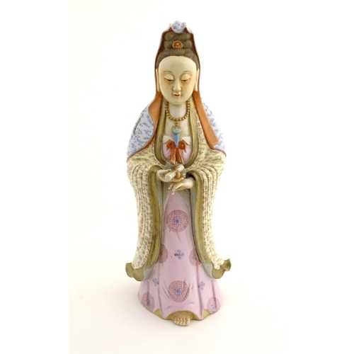 12 - A Chinese famille rose standing figure of Guanyin, the Buddhist bodhisattva associated with compassi...