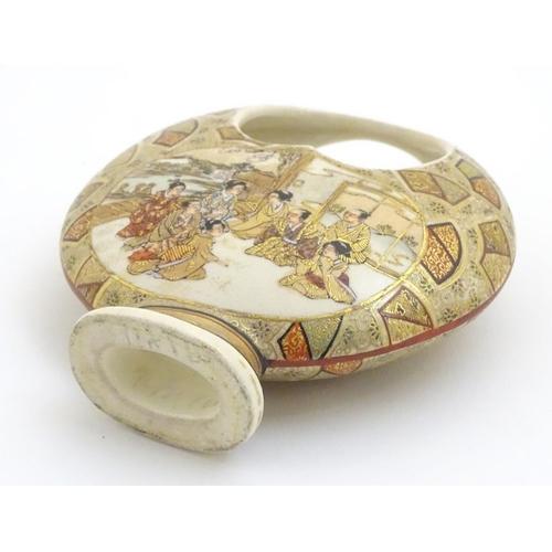 19 - A Japanese satsuma moon basket vase with hand painted decoration depicting figures seated around imp...