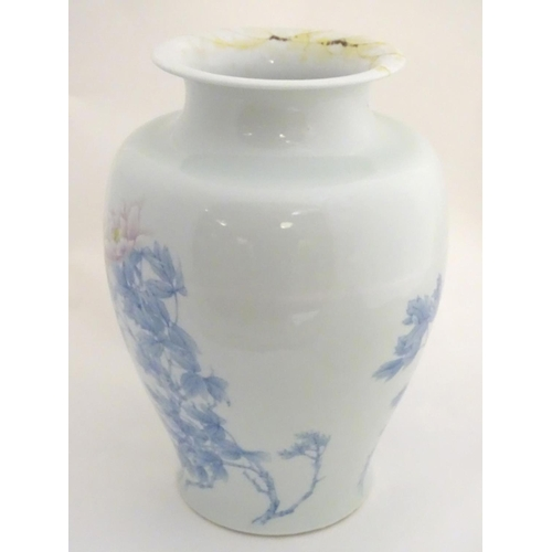 26 - A Japanese Inoue Ryosai baluster vase with a flared rim, decorated with blue branches and leaves and...