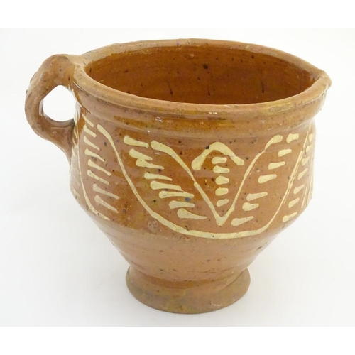 49 - An 18th / 19thC French jug / vessel with a side handle and narrow base, with slipware decoration. Ap...