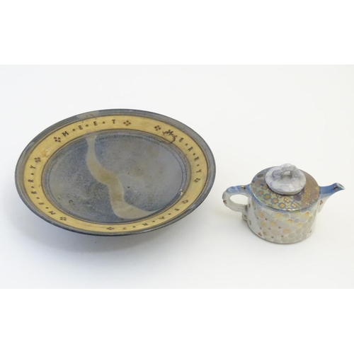 51 - A studio pottery dish with a blue ground, with banded decoration impressed with the saying Merry Mee...