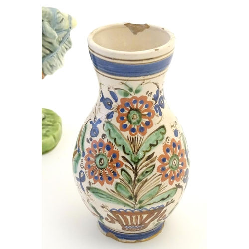 52 - A Continental faience single handed vase / jug with a bulbous body and a flared rim, decorated with ...
