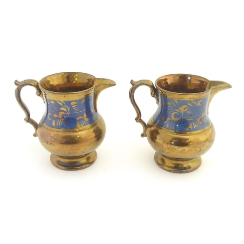 53 - A pair of Victorian copper lustre ware jugs with banded cobalt foliate decoration. Approx. 5 ½'' hig...