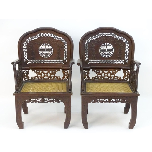 1072 - A pair of Chinese hardwood armchairs with pierced and carved backrests, fretwork supports and caned ...