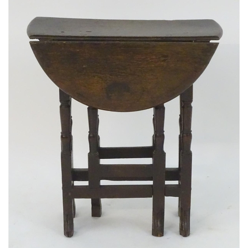 1078 - A small 18thC oak gate leg table of peg jointed construction with drop flaps opening to form an oval...
