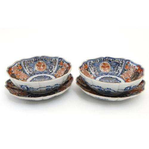 15 - A pair of Japanese Imari plates and matching pair of bowls, having decorative floral and foliate pan...