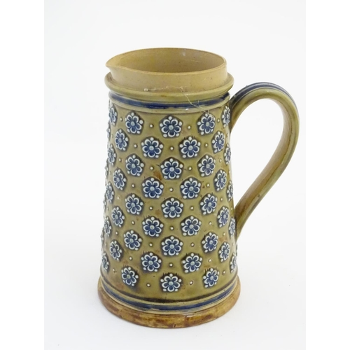 31 - A 19thC Doulton Lambeth jug decorated with flowers in relief designed by Louisa Matterson. Bears Dou...
