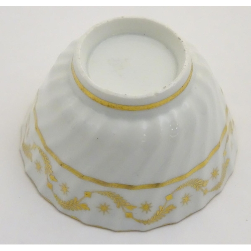 54 - A 19thC white porcelain tea bowl with ribbed sides and gilt decoration of stylised foliage and stars...
