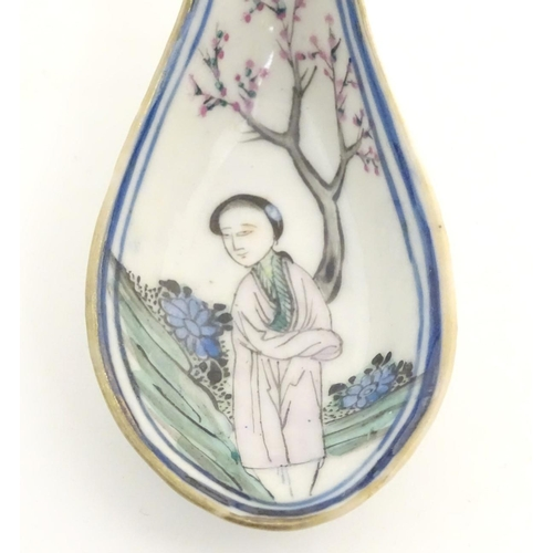 14 - A Chinese famille rose soup spoon decorated with a figure in a landscape with a cherry blossom tree....
