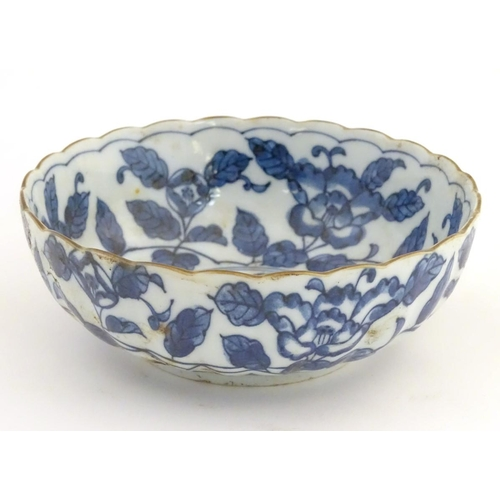 20 - A Chinese blue and white bowl with a lobed rim, decorated with flowers and foliage. Character marks ...