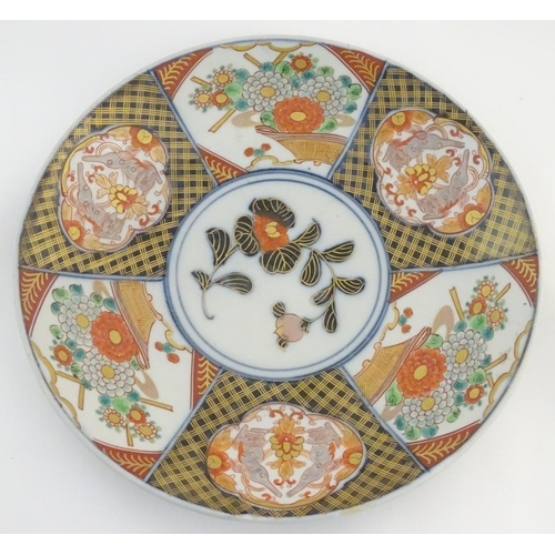 20A - A Japanese Imari charger with panelled decoration decorated with flowers and scrolling foliage, with...