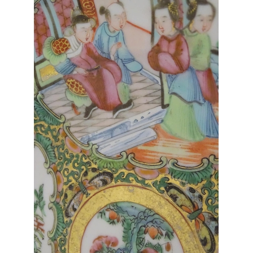 23 - A Chinese Cantonese famille rose plate with panelled decoration depicting figures in an interior and...