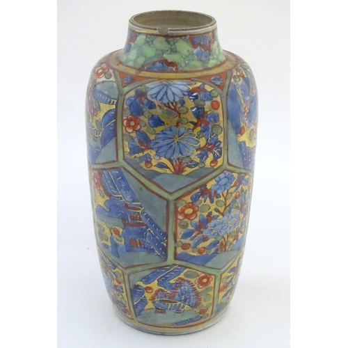 23A - An Oriental vase with hexagonal panelling depicting landscapes, and flowers with scrolling foliage, ...
