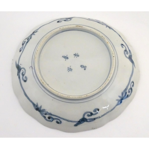 24 - A Chinese plate with a lobed rim, decorated with a landscape with stylised quail birds. Scrolling fo...