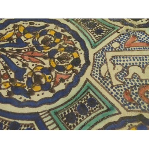 28 - A Moroccan charger with panelled geometric designs with lotus and leaf shaped cartouches with stylis...