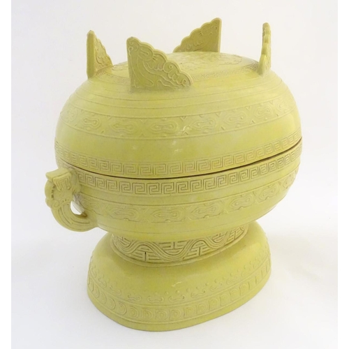 3 - A Chinese yellow ground lidded pot raised on a foot, with twin handles formed as stylised elephant h...