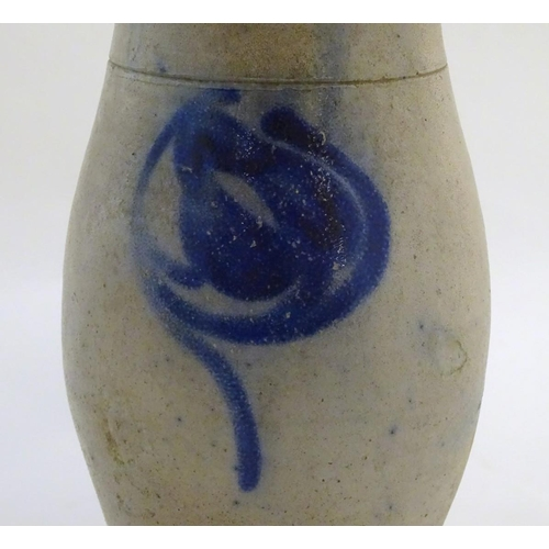44 - A studio pottery vase with a single handle and stylised blue flower decoration. Incised 21 under han...