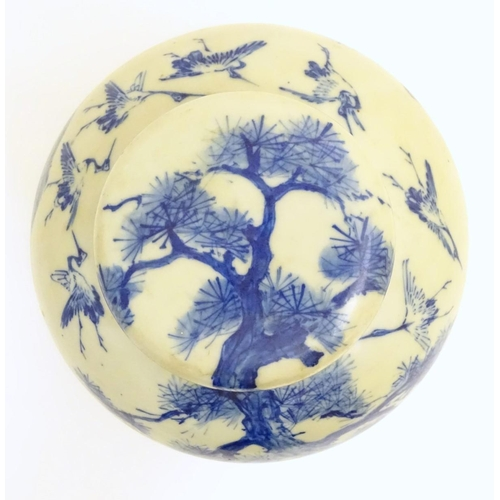6 - A large blue and white Japanese lidded ginger jar decorated with a sage sat by a tree in a landscape...