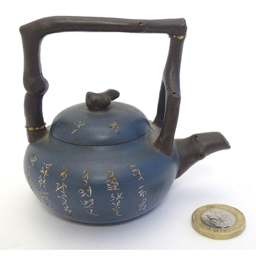 7 - A small Chinese Yixing earthenware / clay teapot and cover with a blue ground, the handle modelled a...