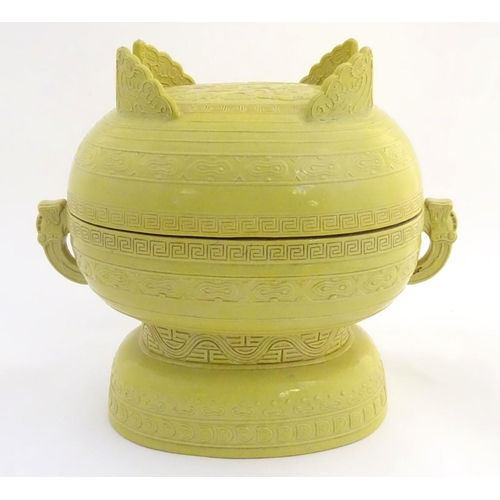8 - A Chinese yellow ground lidded pot raised on a foot, with twin handles formed as stylised elephant h...