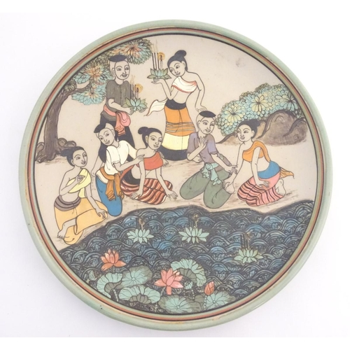 23 - An Oriental plate, the unglazed centre decorated with a group of people in a landscape relaxing near...